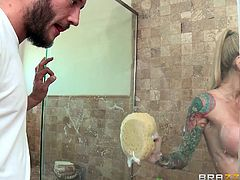 A hot blonde-haired bitch lures her passionate partner in the bathroom, where she is taking a soapy shower. Watch the excited man squeezing her marvelous boobs. Don't miss the inciting tit job, performed by the sexy tattooed milf!