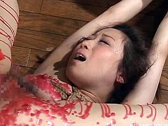 She moans and screams, as her master drops hot candle wax all over her body. It is particularly painful on her nipples and thighs. She is bound tightly with rope, so she cannot escape this painful humiliation.