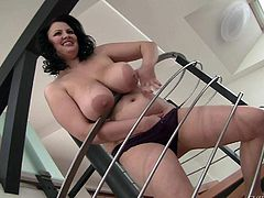 Juicy brunette Barbara Angel dressed in black shows off her huge tits and gets naked on the stairs. She is proud of her massive breasts. She poses topless with smile on her face and then pulls off her panties.