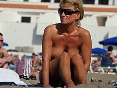 Nice tanned milf with big boobs at the beach