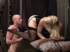 Ash Hollywood is a sexy domina that has her latex outfit on. The blonde pornstars is on top of a guy and she is forcing him to lick her feet. Her moves are strict.
