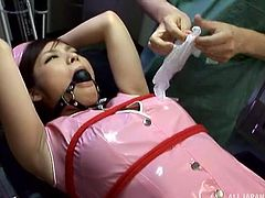 She has been disobeying orders, so the doctor has to tie this latex nurse down. Her mouth is gaged, as she has a vibrator rubbed on her nipples and clit. He spreads her legs wide, so he can see her lovely hairy twat.