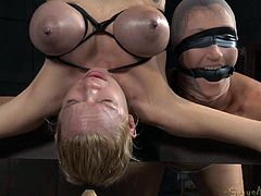 Dominating two sluts at once is not very odd, but the way it's done here kind of is. Rain is hanging upside-down, while her executor stimulates her with a big vibrator. Wenona is strapped to the beam near, where Rain's head dangles, being able to neither see nor say anything, because of her bondage.