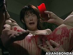 Asian slut is getting her wet pussy poured with hot wax. She loves the way it hurts but the pain is brief and it is getting her off just the right amount.