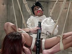 Busty redhead mistress Bella Rossi, brutally punishing her ebony sex slave Kira Noir. Kira is tied with rope, suspended, her mouth is stuffed with the gag, while she is dressed in straitjacket and her pussy is stimulated with the help of vibrator. Watch hot lesbian ass spanking and enjoy!