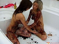 Lesbians covered in chocolate sauce lick it off of each other