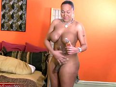 Big and curvy ebony TS Courtney is wearing a tight dress and pink lingerie that show off her fleshy body. Massaging oil into her massive boobs, her black dick grows big and hard and she continues...