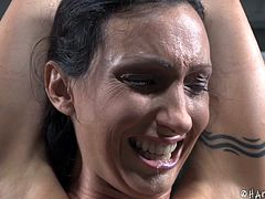 Wenona is famous for being an Ultimate Surrender champion. What she's doing now, is extremely physical as well. She's tied with her legs split as wide as possible, arms above her head, clamps on her nipples attached to strings going to the floor. She screams in pain and moans, when he treats her.