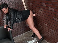 Lady in sexy leather clothes goes crazy over the fake gloryhole dick