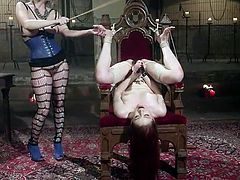 Cherry has Violet tied up to this chair. She's whipping her and teasing her, taunting her with mean words. She softens up, as she kisses her submissive, then releases her, to get more comfortable, as she gets boned with the strap-on.