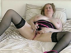 Kimmy's libido is on fire, and she knows just how to slake her lust. Feeling confident and beautiful in sexy lingerie and stockings, this mature woman lies back in bed and fondles her big tits. Spreading her legs, she flicks her clit and fucks her twat with her fingers.