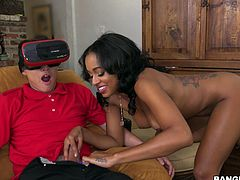 This guy is stuck on that virtual reality headset. He's watching a hot black chick standing naked in front of him, but there's a real one in the room, and she starts sucking his dick! Will he figure out that it is actual reality, and not virtual?