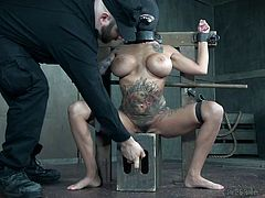 Busty Lily is placed in a special bondage device, legs are spread apart, her head is covered in black canvas, with only one hole for her mouth to breath. A silent man in black touches her tits negligently and starts to stimulate her pussy with the help of electric vibrator, before fingering her asshole rudely.