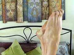 Kelly Madison uses her sexy feet to make a man's prick pulsate