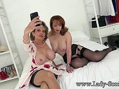 Mature sexy married and horny Lady Sonia invites her sensual redhead friend to join in on the fun. Both dressed in garters and thigh-highs take turns undressing each other out of their lingerie as they play on her bed.