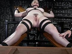 First, the busty short-haired lesbian babe Riley Nixon, was tied to a special wooden bondage device. While bound, when she was not able to move any more, her dominating lesbian lover pinched Riley's hard nipples with metal clamps and fingered her wet pussy really deep...