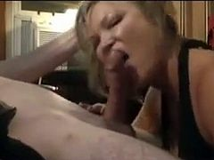 A pov shot of a lovely blonde milf giving some naked dude a suck job in her black dress.